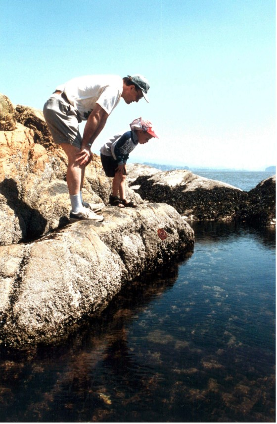 The author and his son looking at tidal pool life, Lighthouse Park, North Vancouver, BC, 1997 (Photo L.M. Friskie).